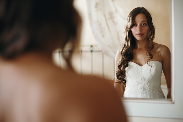 Young nice bride looking in mirror