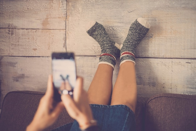 幸せで面白い靴下で彼女の足元にスマートフォンで写真を撮るソファの上の若い素敵な白人女性。楽しいライフスタイルのホームデイリーシーン。友達と人生を共有するコンセプト