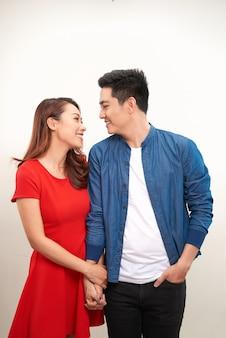 スタジオでポーズをとって、感情やジェスチャーを表現し、笑顔で若い素敵なカップル