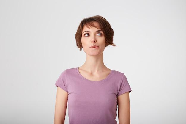 空白のtシャツを着た若い素敵な疑わしい短髪の女性は脇に見え、唇を噛み、考えています。白い背景の上に立っています。