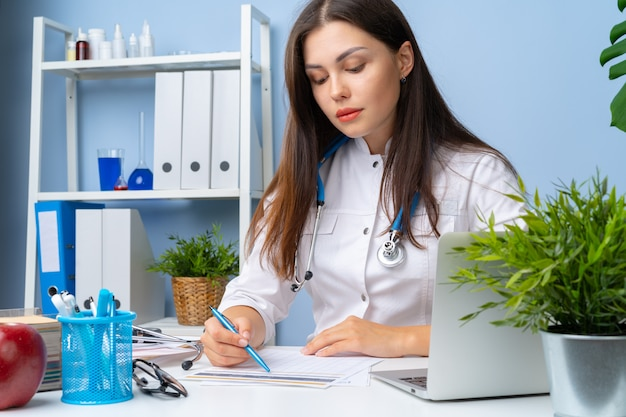 Young nice female doctor working in her office