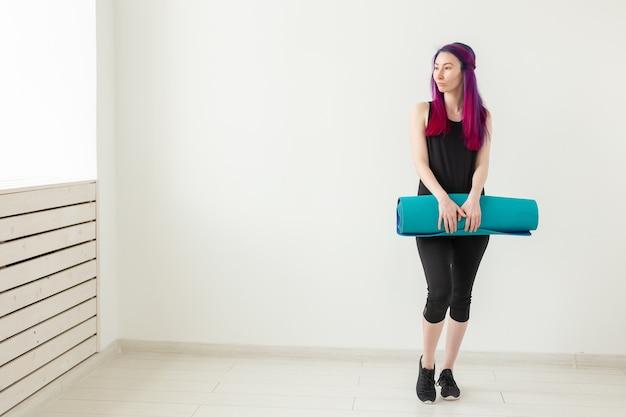 白い部屋でポーズをとるスポーツマットを手に持っている色の髪を持つ若い素敵な女の子のヒップスター