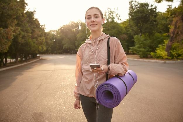 Молодая симпатичная девушка гуляет после йоги в парке, держит смартфон в руке и слушает музыку в наушниках, чувствует себя прекрасно и улыбается.