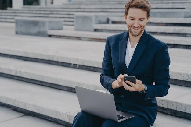 Молодой симпатичный мужчина-предприниматель в стильном костюме с помощью смартфона сидит на улице с ноутбуком