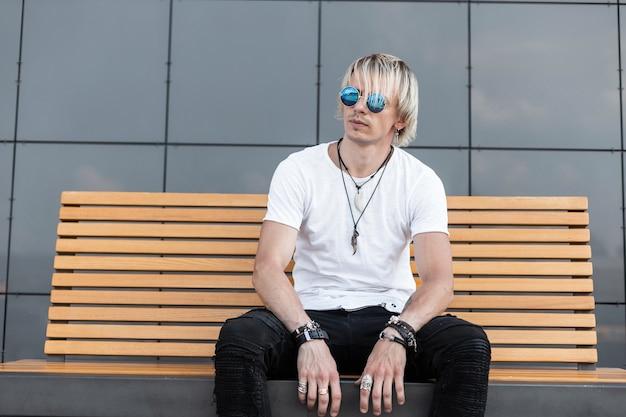 白いtシャツの黒のジーンズの青いサングラスの若い素敵な男は、通りのモダンな灰色の壁の近くのヴィンテージの木製のベンチに座っています。屋外でハンサムな男のモデル。スタイリッシュな夏のメンズウェア。