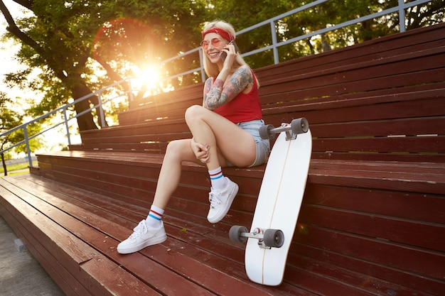 Young nice smiling blonde woman with tattooed arms, talking to his boyfriend on smartphone, waiting for date. wears in red t-shirt, denim shorts, with knitted bandana on her head, in red glasses.