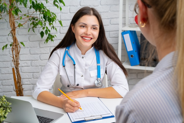 Young nice woman doctor having a conversation with her patient in hospital
