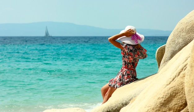 海岸の帽子をかぶった若い素敵な女性