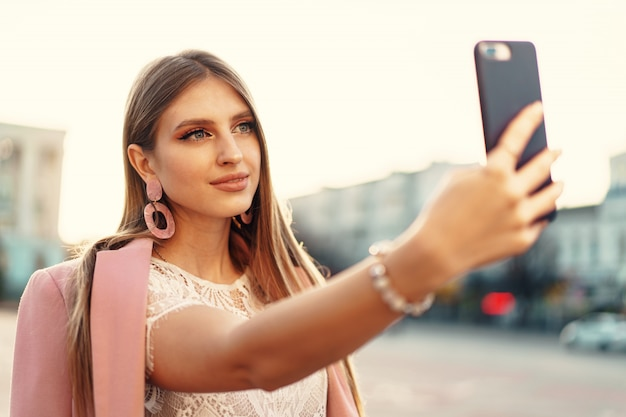 Young nice woman making selfie in the street