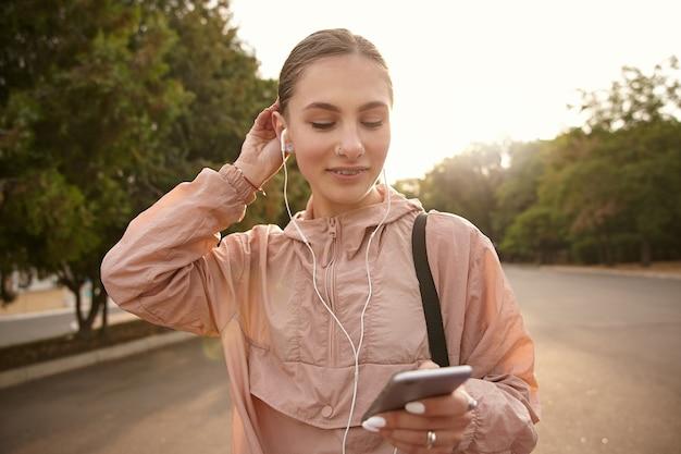 Молодая симпатичная женщина гуляет в парке, держит смартфон в руке и болтает с другом, слушает музыку в наушниках, чувствует себя круто и улыбается.