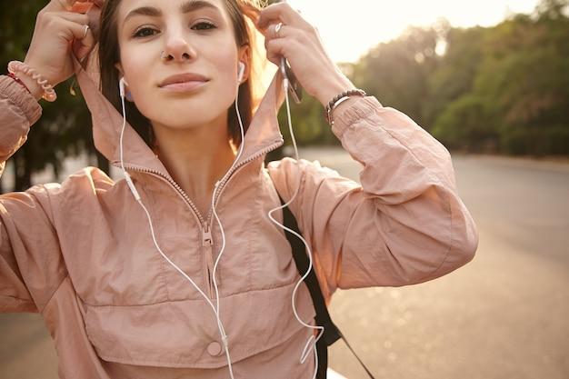 公園を歩いて、ヘッドフォンで音楽を聴いている若い素敵な女性は、クールで素晴らしい気分で、フードをかぶってカメラを見ています。