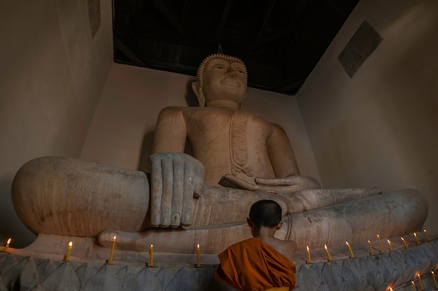 Young novice monk praying with candles in front of buddha statue inside old pagoda, ayutthaya, thailand.