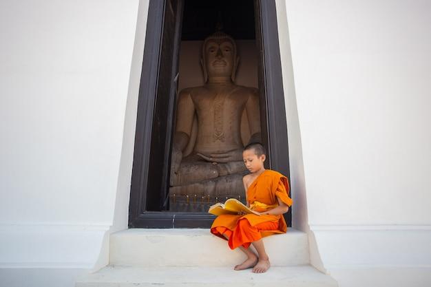 Young novice monk reading a book in wat phutthai sawan temple, ayutthaya, thailand