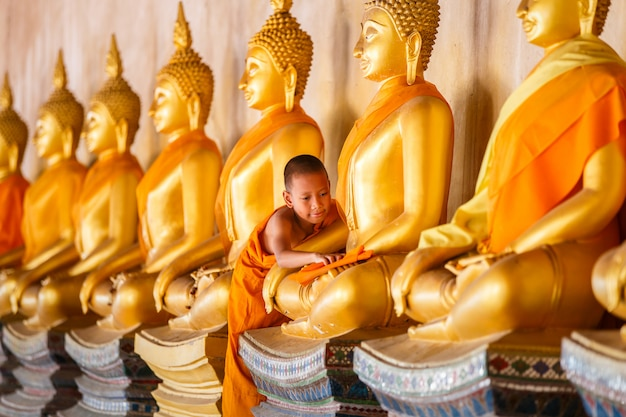 Young novice monk scrubbing buddha statue at old temple in myanmar