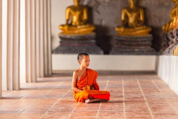 Молодой монах-новичок сидит для медитации в храме ват пхуттайсаван, аюттхая, таиланд