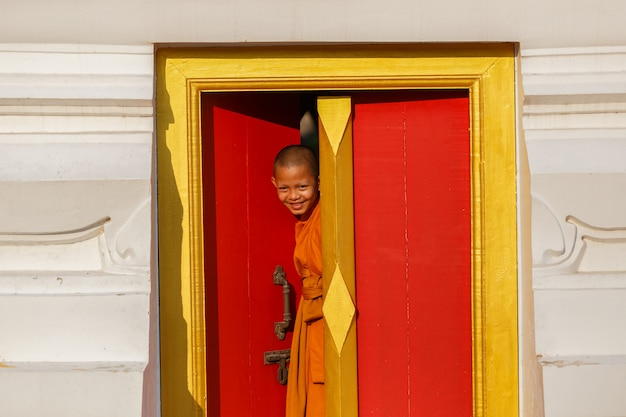 Young novice monk smile in monastery