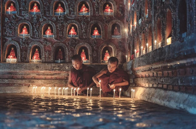 Young novice monks lighting up candlelight inside a buddhist temple, low light setting, shan state, myanmar.