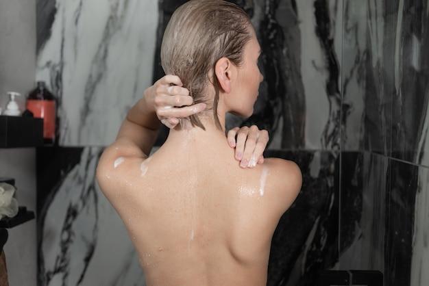누드 아가씨 집에서 샤워를하고 뒤에서 볼 수 있습니다. 물줄기가 피부 아래로 흐릅니다.