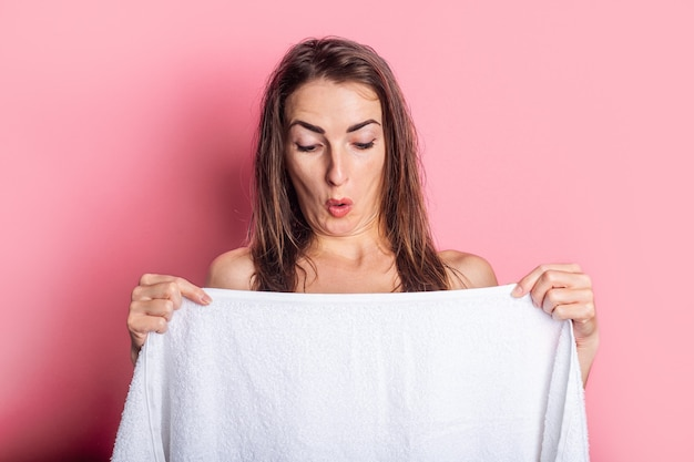 Young nude woman looking at breasts covered with towel on pink background.