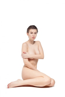 Young nude woman sitting on the floor