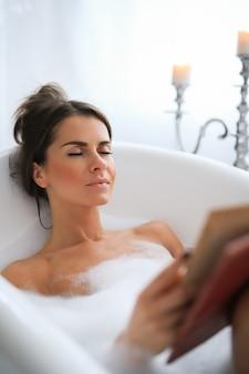 편안한 거품 목욕을하고 책을 읽는 젊은 누드 여자