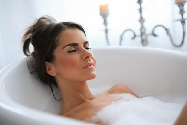 편안한 거품 목욕 젊은 누드 여자