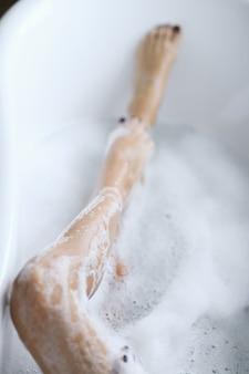 Молодая обнаженная женщина принимает расслабляющую пенную ванну