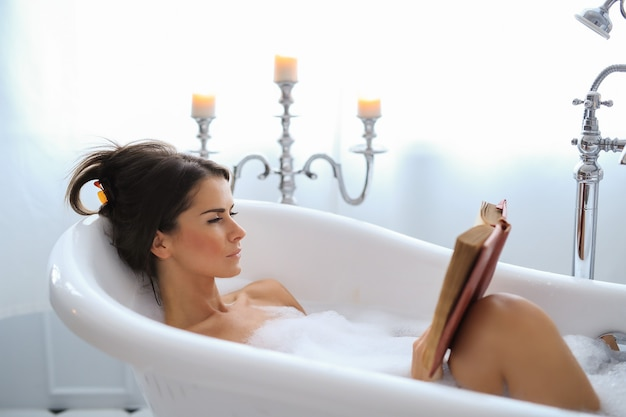 Young nude woman taking a relaxing foamy bath and reading a book