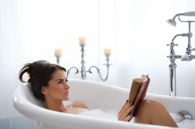 Giovane donna nuda facendo un rilassante bagno schiumoso e leggendo un libro