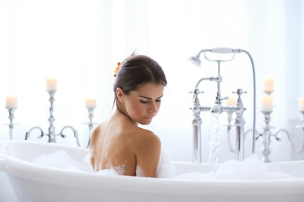 Giovane donna nuda che cattura un bagno schiumoso rilassante