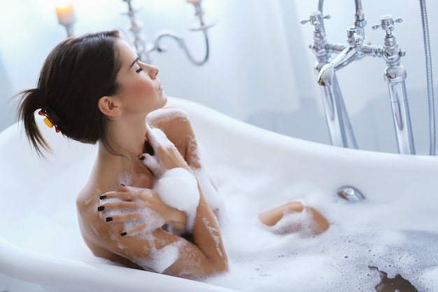 Young nude woman taking a relaxing foamy bath