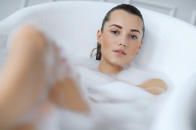 Young nude woman taking a relaxing foamy bath