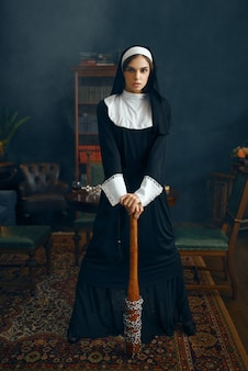 Young nun in a cassock holds a baseball bat wrapped in a chain, vicious desires. corrupt sister in the monastery, religion and faith, sinful religious people, attractive sinner