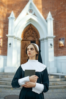 Young nun in a cassock holds a book in church