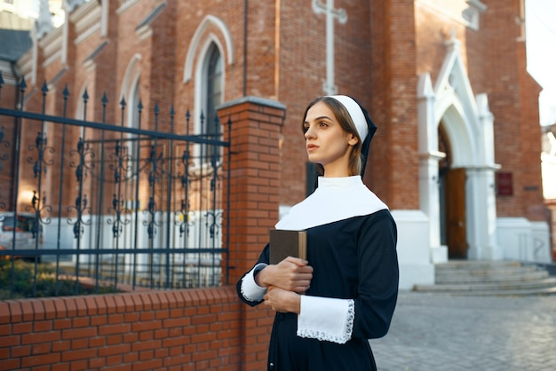 Young nun in a cassock holds a book