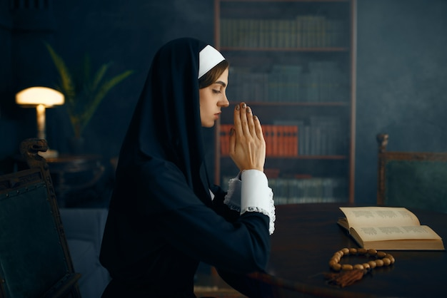 Young nun in a cassock prays crossed her arms
