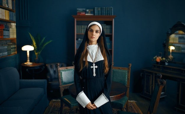 Young nun in a cassock with a cross around her neck holds a book. the sister is preparing for prayer in the monastery