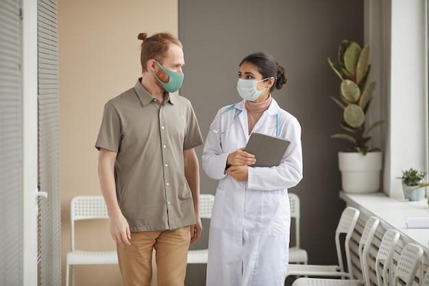 Молодая медсестра и пациент в защитных масках смотрят друг на друга во время прогулки по коридору в клинике