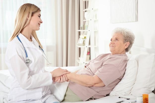 Young nurse examining elderly woman at home