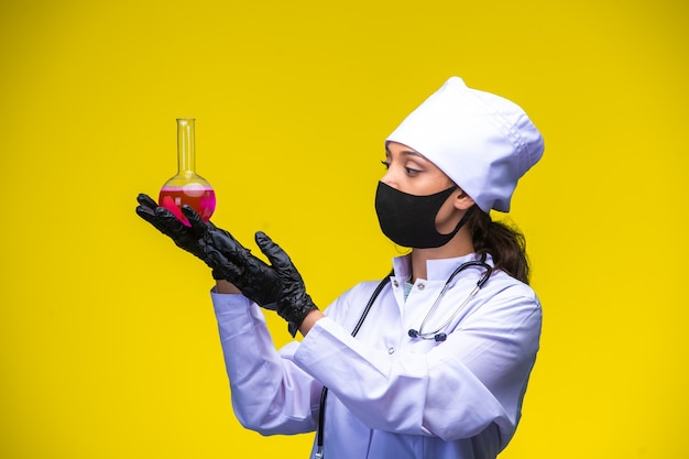 Young nurse in face and hand mask holds chemical flask with both hands.