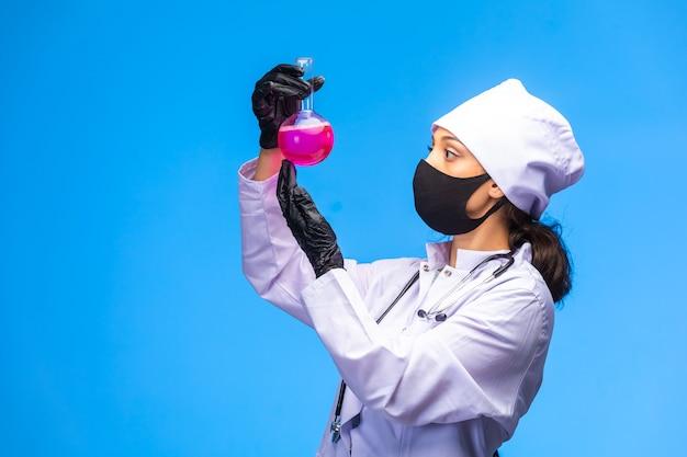 La giovane infermiera in maschera per il viso e la mano tiene un pallone di prova e segue la reazione chimica.