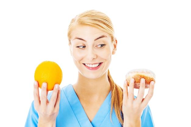 白い背景の上に分離された甘い食べ物とオレンジを保持している若い看護師