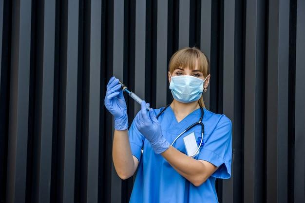 薬瓶と注射針を持つ若い看護師。注射器に薬を拾う医師。