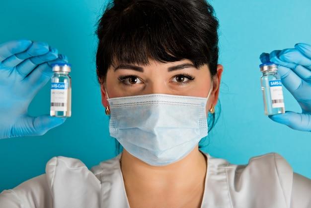 青い背景にcovid-19コロナウイルスワクチンの2つのバイアルを保持している医療マスクの若い看護師。閉じる。