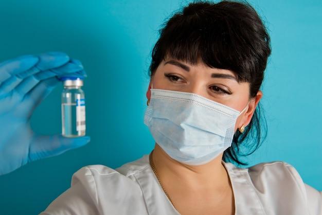 青い背景にcovid-19コロナウイルスワクチンのバイアルを保持している医療マスクの若い看護師。閉じる。