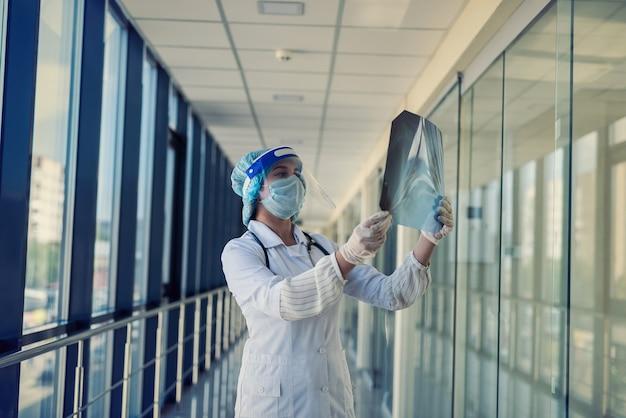 보호 복 및 얼굴 방패 검사 가슴 xray 이미지, covid19에서 젊은 간호사. 감염병 세계적 유행