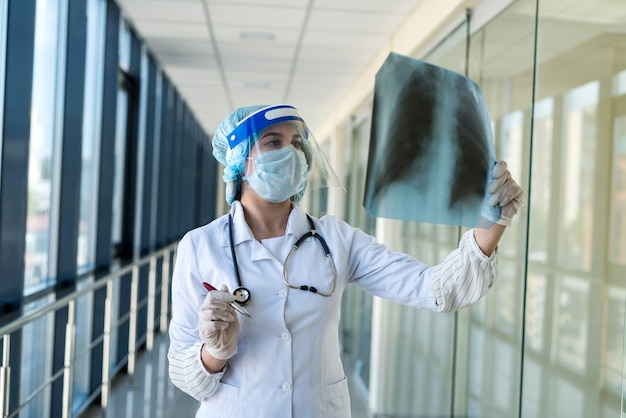보호복을 입은 젊은 간호사와 얼굴 쉴드가 흉부 엑스레이 이미지, covid19를 확인합니다. 감염병 세계적 유행