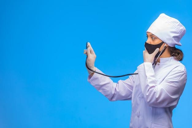 검은 얼굴 마스크에 젊은 간호사는 청진으로 환자를 확인합니다.