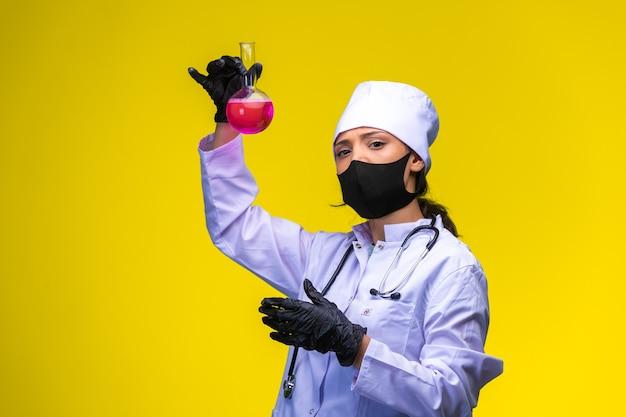 Молодая медсестра в маске для лица и рук следит за реакцией в колбе и показывает ее