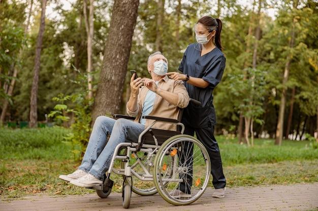 Молодая медсестра в защитной маске и маске помогает пожилому инвалиду в инвалидной коляске